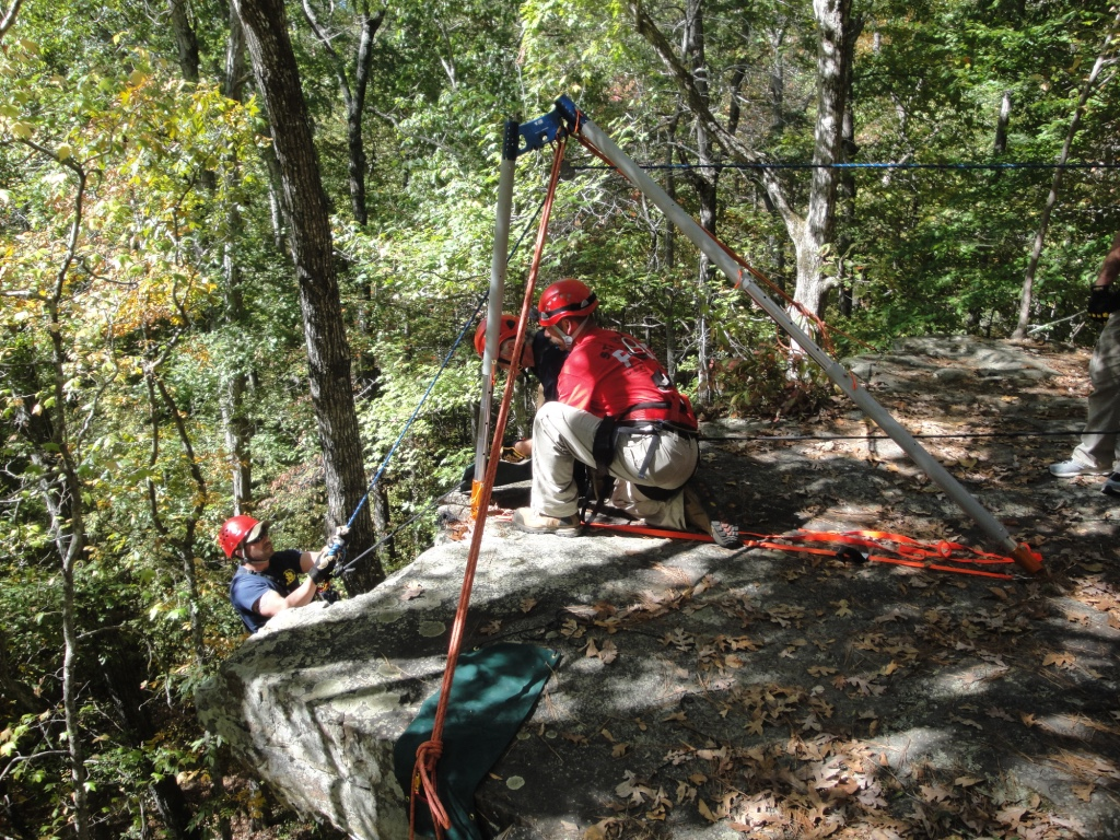 Firefighter participating in Advanced Wilderness Rope Rescue Course is lowered using a sideways A-frame artificial high directional.