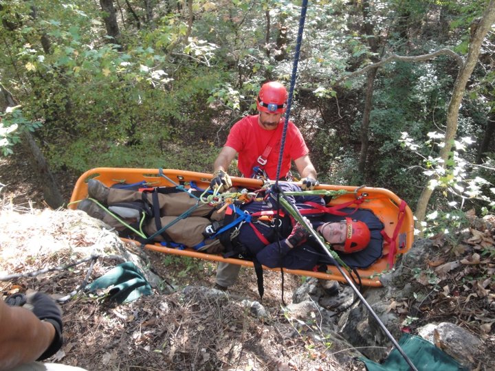 Firefighter participating in Advanced Wilderness Rope Rescue Course attends patient on a lower.